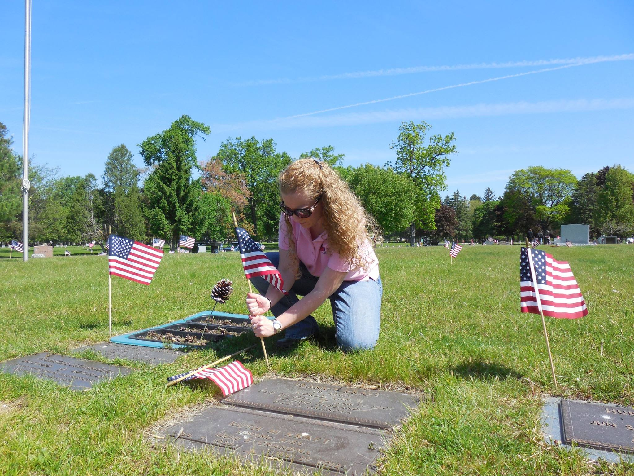 Cleaning military stones and placing flags for Memorial Day